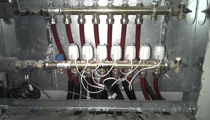 Rozdělovač podlahového topení s instalovanými elektrickými ventily.